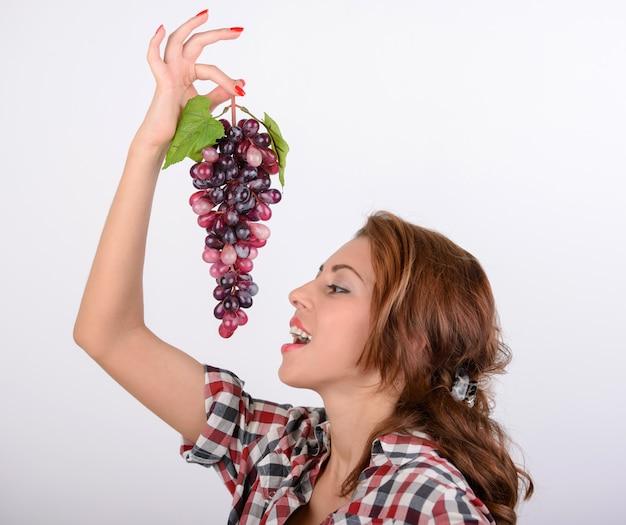 Diätkonzeptporträt der jungen frau mit roter traube