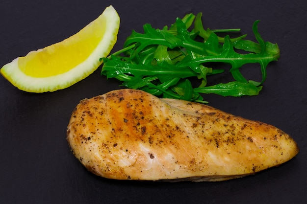 Diätküche - gegrillte hühnerbrust mit rucolablättern und zitrone auf dunklem hintergrund.