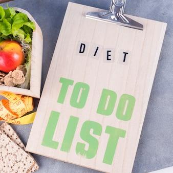 Diätliste mit gesundem essen auf dem tisch