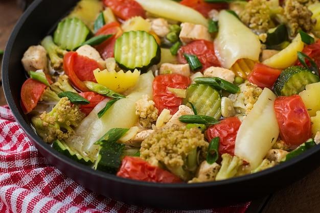 Diätmenü. gedämpftes gemüse mit hähnchenfilet in der pfanne auf dem holztisch.