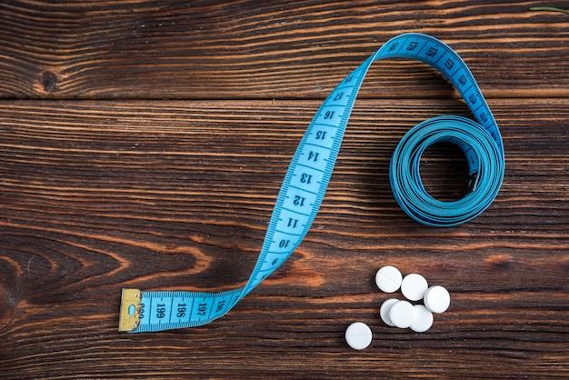 Diätpillen und klebeband auf holz