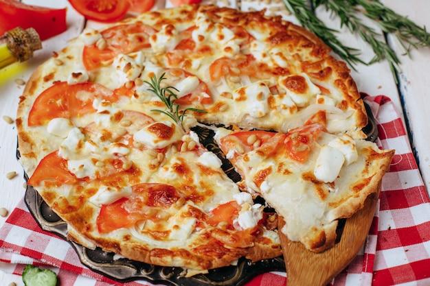 Diätpizza mit tomatenkäse und nüssen auf dem tisch