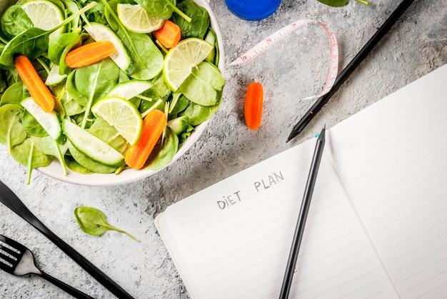 Diätplan gewicht verlieren konzept, frischer gemüsesalat mit gabel, messer, notizblock, grauer steintischkopierraum draufsicht