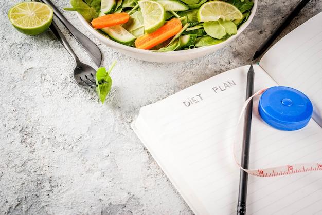 Diätplan gewicht verlieren konzept, frischer gemüsesalat mit gabel, messer, notizblock, grauer steintischkopierraum