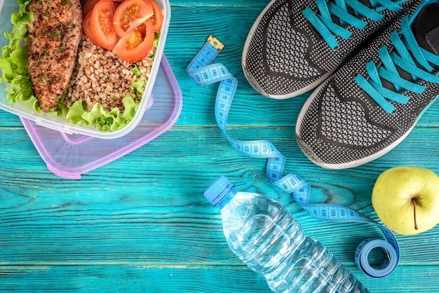 Diätplan, menü oder programm, maßband, wasser, brotdose mit hühnerbrust, buchweizen, tomaten und apfel auf blauem holz, flach liegen