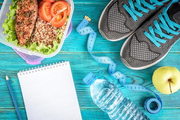 Diätplan, menü oder programm, maßband, wasser, brotdose mit hühnerbrust, buchweizen, tomaten und apfel auf blauer, flacher lage