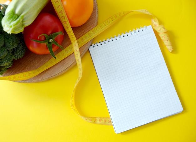 Diätplanmodell mit frischem gemüse, maßband und leerem notizblock auf gelbem hintergrund. gesunder ernährungsplan. diät und essensplanung. platz für text. flach liegen.