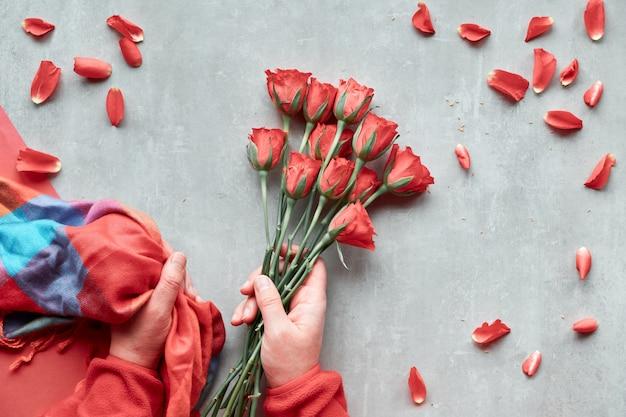 Diagonales geometrisches papier auf stein. flache lage, weibliche hände halten rote rosen und lebhaften trendigen farbschal, verstreute blütenblätter. draufsicht, konzept für valentinstag, geburtstag oder muttertag.