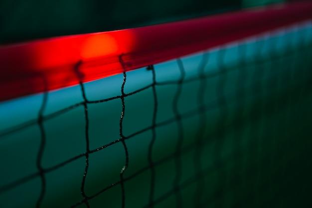 Diagonales tennisnetz mit rotem streifen im grünen hartplatz, tenniswettbewerbkonzept