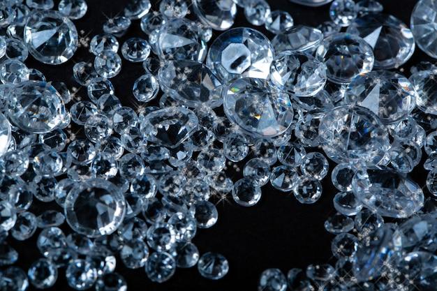 Diamanten auf schwarzem hintergrund. blaue und weiße brillante edelsteine, seitenansicht mit kopienraum für ihren text. studioaufnahme, selektiver fokus. haufen von künstlichen diamanten. kunststoff in granulat. streuung von kristallen