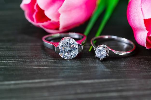 Diamanthochzeitsringe mit tulpenblume auf schwarzem hintergrund