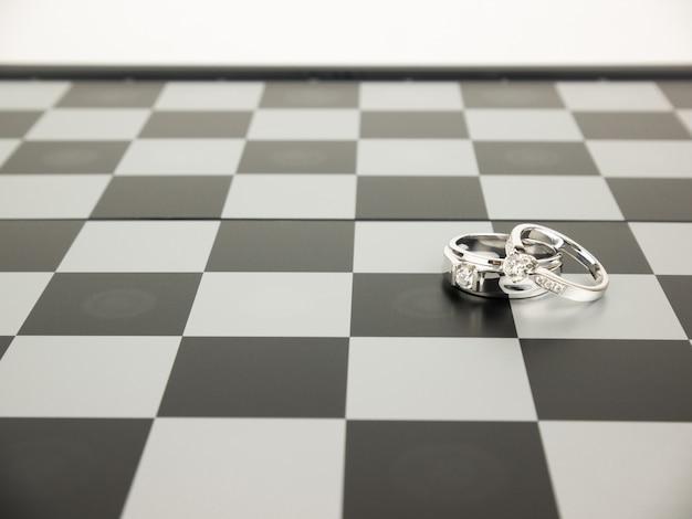 Diamantring mit könig- und königinschach auf dem brett, hochzeits-konzept.