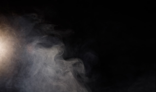 Dichte flauschige hauche von weißem rauch und nebel auf schwarzem hintergrund
