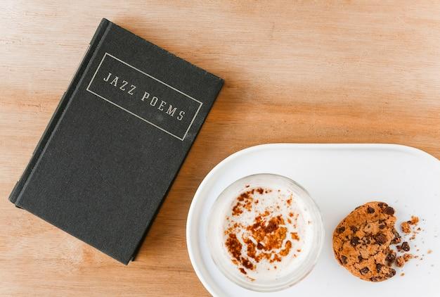 Dichterbuch mit kaffee und gegessenen plätzchen auf platte