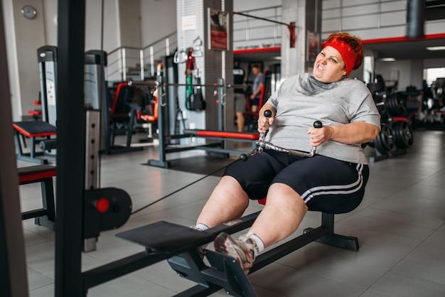 Dicke frau, aktives training auf übungsmaschine im fitnessstudio. kalorien brennende, fettleibige weibliche person im sportverein