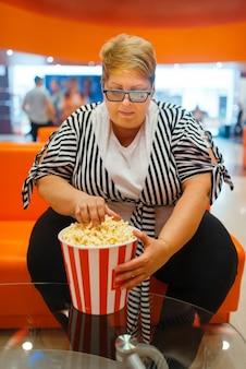 Dicke frau, die popcorn im kinosaal hält