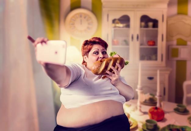 Dicke frau isst sandwich und macht selfie, fettleibigkeit, übergewichtige menschen. ungesunder lebensstil, fette frau
