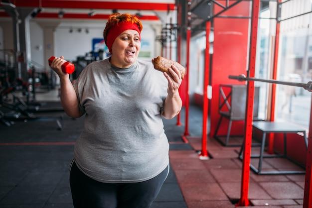 Dicke frau mit fast food und hantel in händen, motivation, hartes training im fitnessstudio. kalorienverbrennungskonzept, fettleibige weibliche person im fitnessclub, fettverbrennung, sport gegen ungesundes essen