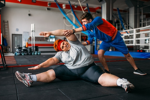 Dicke frau, übung auf dem boden mit ausbilder, training im fitnessstudio. kalorien brennende, fettleibige weibliche person im sportverein