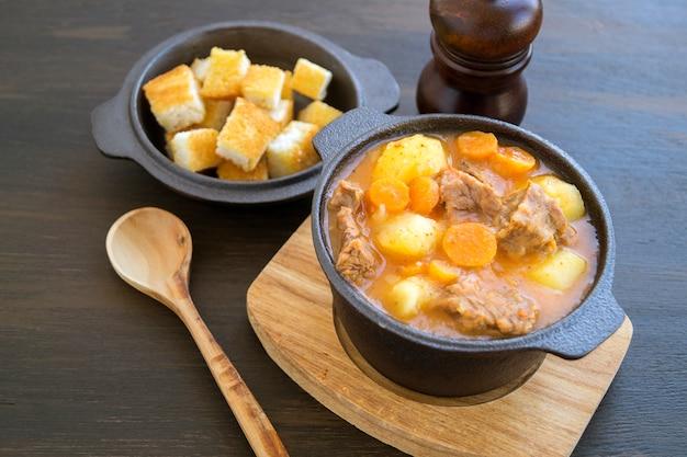 Dicke ungarische suppe, das gulasch. auf dunklem hintergrund.