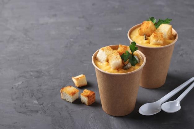 Dicke vegane kürbiscremesuppe mit samen und croutons in einwegbechern bastelpapier. suppe zum mitnehmen. gesunde lebensmittellieferung. essen zum mitnehmen.