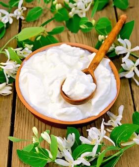 Dicker joghurt in einer tonschale mit löffel und weißen geißblattblüten