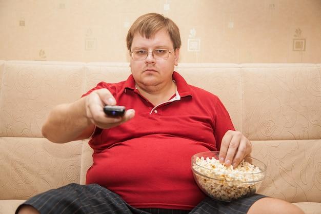 Dicker mann beim fernsehen popcorn essen