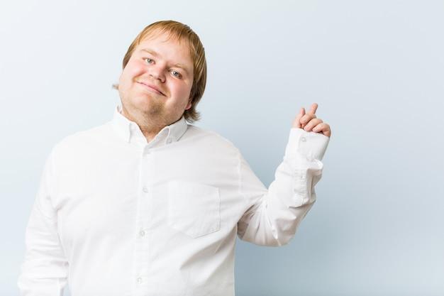 Dicker mann der jungen authentischen rothaarigen, der mit dem zeigefinger weg freundlich zeigend lächelt.