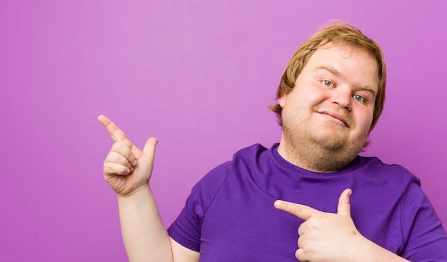 Dicker mann der jungen authentischen rothaarigen, der mit den zeigefingern auf a zeigt und aufregung und wunsch ausdrückt.