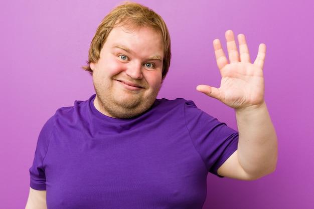 Dicker mann der jungen authentischen rothaarigen, der nette darstellende nr. fünf mit den fingern lächelt.