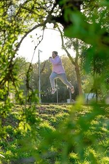 Dicker mann in sportbekleidung, der im grünen park mit sonnenlicht von hinten springt