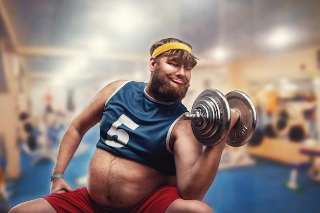 Dicker mann macht übungen mit einer hantel im fitnessstudio
