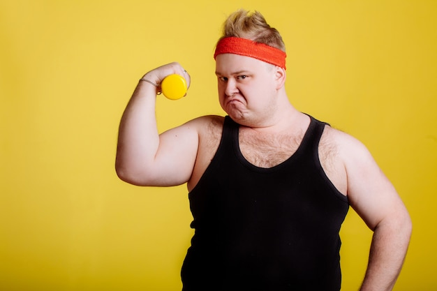 Dicker mann mit hantel auf gelber wand. motivation für dicke leute