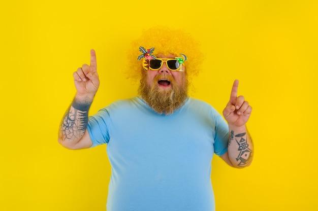 Dicker mann mit perücke im kopf und sonnenbrille zeigt mit händen etwas an