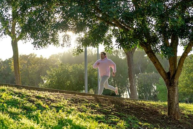 Dicker mann trägt rosa und graue sportkleidung und treibt sport im park