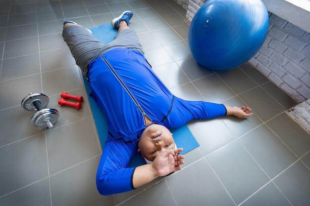 Dicker mann trainiert im fitnessstudio