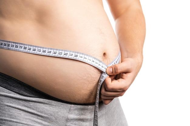 Dicker mann überprüft sein körperfett mit maßband auf weiß oder fettleibigkeit