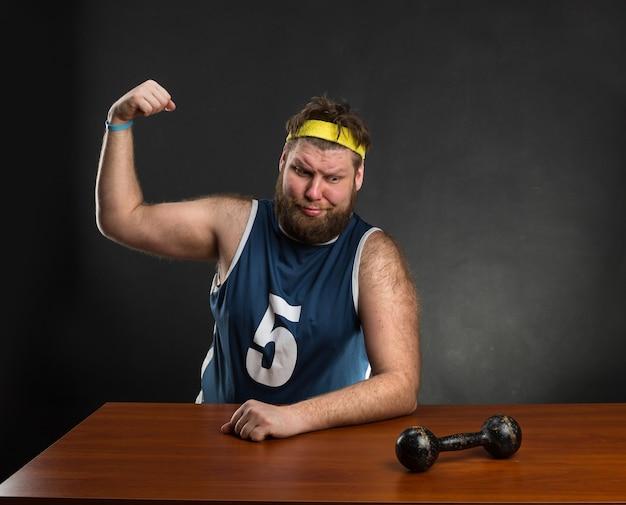 Dicker mann zeigt seine muskeln mit einer hantel am tisch