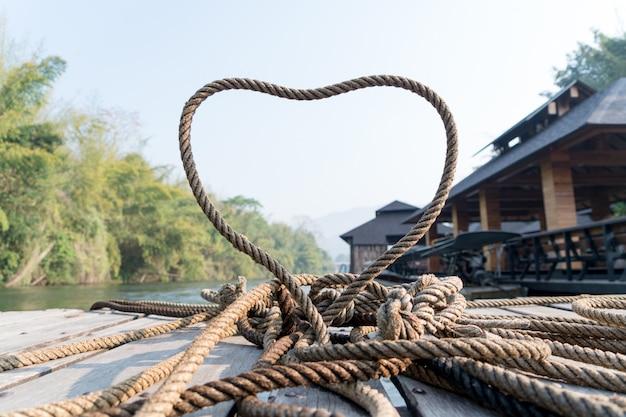 Dickes seil bindet die herzform auf der holzterrasse