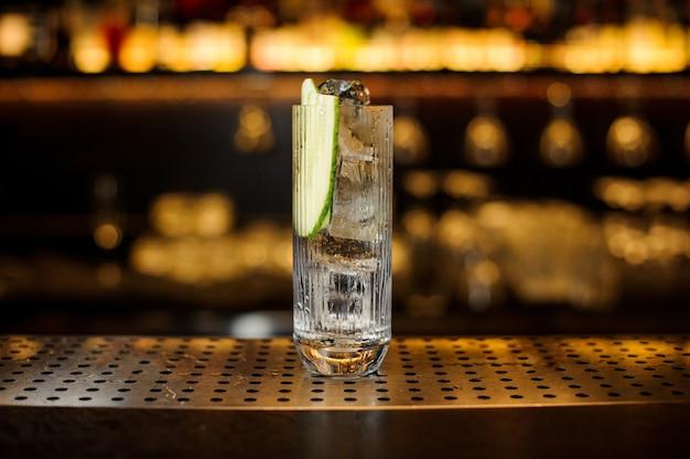 Dickwandiges vintage-cocktailglas mit eiswürfeln, dekoriert mit gurken, stehend auf dem leeren barständer aus stahl