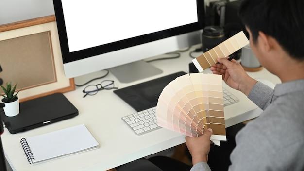 Die abgeschnittene aufnahme eines grafikdesigners oder fotografen arbeitet mit einer farbpalette und wählt farbmuster für ein designprojekt am schreibtisch aus.