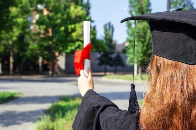 Die absolventin hob ihre hände und feierte mit einem zertifikat in der hand und fühlte sich so glücklich am anfangstag