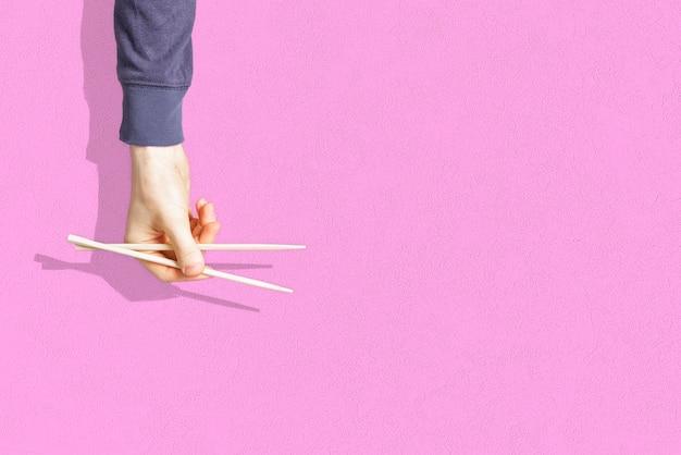 Die abstrakte hand, die das leere paar hölzerne essstäbchen hält, lokalisiert auf farbigem hintergrund,