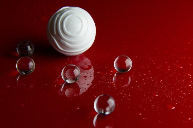 Die abstrakte kristallkugel auf rotem glänzendem bodenhintergrund.