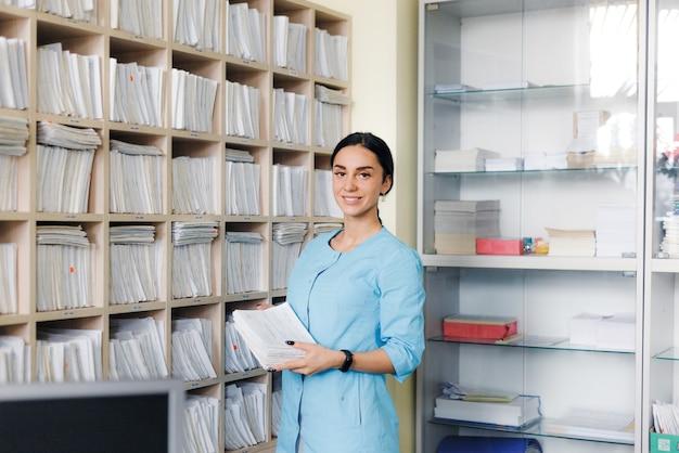 Die administratorin der medizinischen klinik findet die erforderliche patientenkarte in der schublade des racks und überprüft die korrespondenz des nachnamens. ärztezentrum