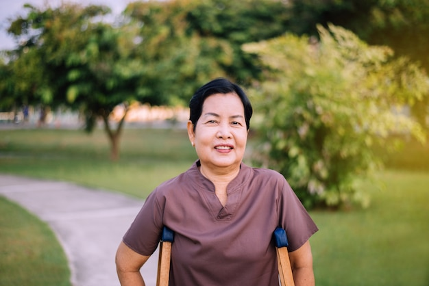 Die ältere asiatische frau des patienten, die krücken verwendet, unterstützt gebrochene beine für das gehen am öffentlichen park am morgen, physiotherapiekonzept