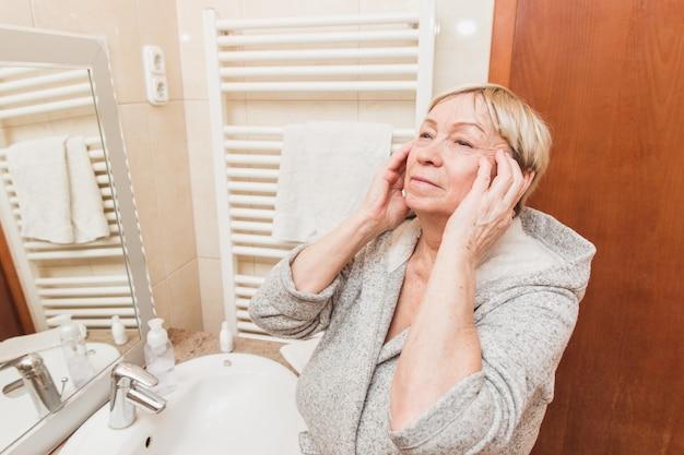Die ältere frau, die ihre weiche gesichtshaut berührt und tut massage