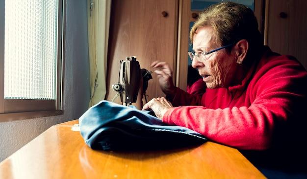 Die ältere frau, die nähmaschine verwendet, konzentrierte sich mit dem natürlichen licht, das durch das fenster kommt