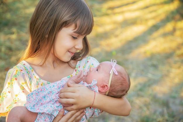 Die ältere schwester hält das neugeborene in den armen. selektiver fokus. menschen.