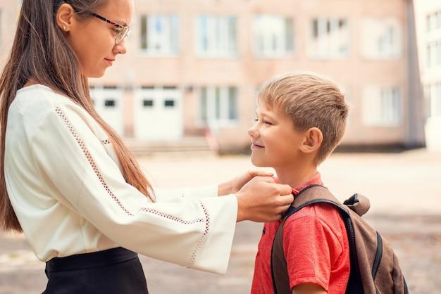 Die ältere schwester hilft ihrem kleinen bruder bei der vorbereitung auf die schule